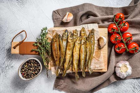 Fried smelt, sprats. Small fried fish. Gray background. Top view. Reklamní fotografie
