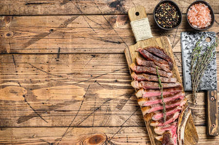 Grilled cowboy or ribeye beef steak with herbs and spices. Wooden background. Top view. Copy space.