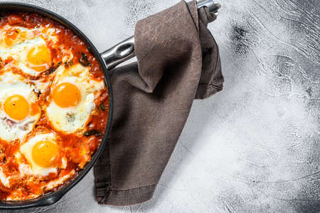 Homemade shakshuka, fried eggs, onion, bell pepper, tomatoes and parsley in a pan. Gray background. Top view. Copy space.