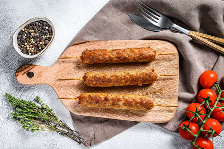 Turkish and Arabic Traditional kebab on cutting board, ground beef, lamb meat. White background. Top view.
