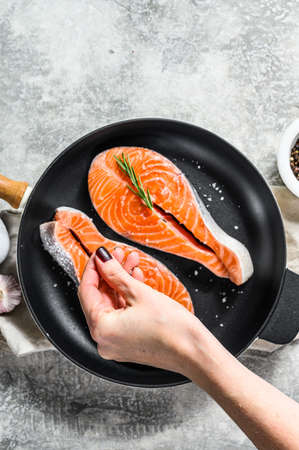 Chef salts raw salmon steak in a frying pan. Healthy seafood. Gray background. Top view. Space for text