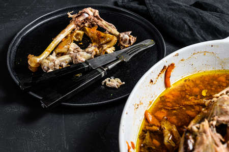 A plate of chicken bones and a chicken skeleton in a baking dish. Leftovers from dinner. Black background. Top view.