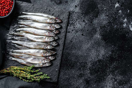 Raw small fish anchovies with pepper and thyme. Black background. Top view. Copy space.