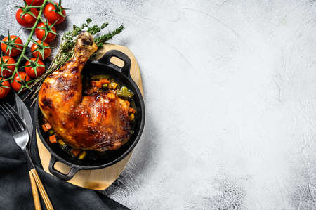 Cooked roasted chicken legs in baking pan. Grilled meat. Gray background. Top view. Copy space.