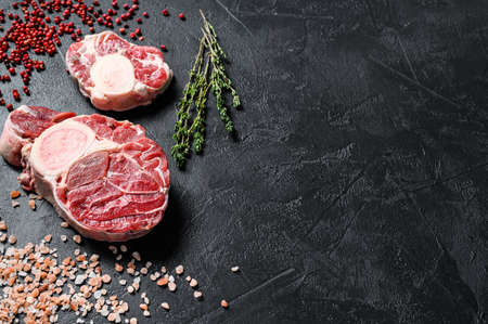 Raw fresh ossobuco con with herbs. osso buco meat. Black background. Top view. Copy space.