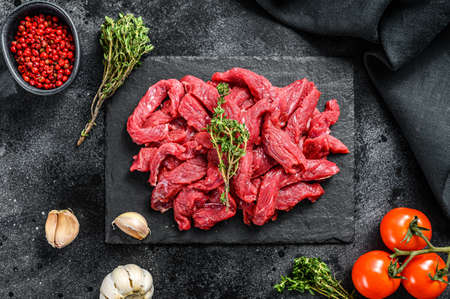 Raw meat cut into thin strips for beef Stroganoff. Black background. Top view. 免版税图像