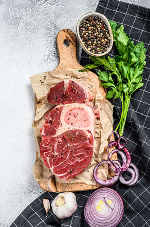 Raw cross cut veal shank, Osso Buco with spices and herbs. OssoBuco meat. Gray background. Top view. Imagens
