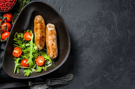 Grilled sausages with tomato and arugula salad. BBQ meat recipe. german food recipe. Black background. Top view. Copy space.