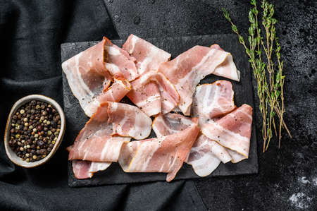 Smoked pork bacon with pepper and thyme. Organic raw meat. Black background. Top view.
