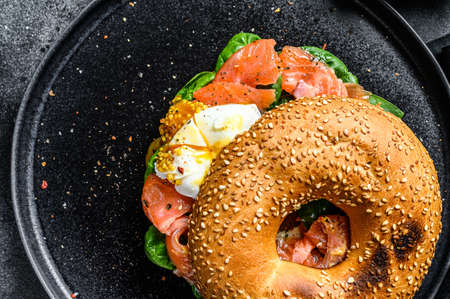 Smoked salmon bagel toasts with soft cheese, spinach and egg. Black background. Top view.