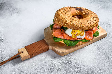 Bagel with salted salmon, cream cheese, avocado and egg. Gray background. Top view.
