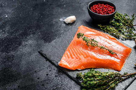 Fresh raw salmon fillet with thyme. Black background. Top view. Copy space. Stock fotó