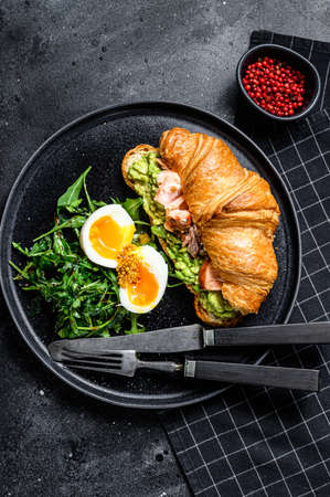 Croissant with hot smoked salmon, avacado, arugula and egg. Black background. Top view. Stock fotó