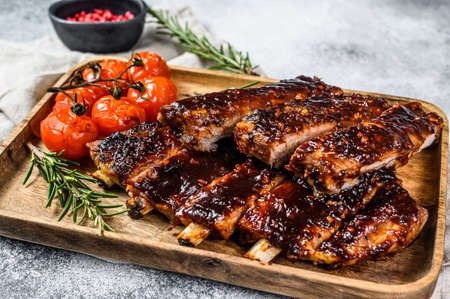 Delicious barbecued ribs seasoned with a spicy basting sauce and served with baked tomatoes. Gray background. Top view. Stock fotó
