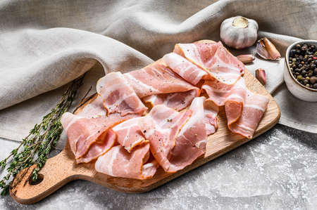 Fresh pork bacon on a chopping Board. Organic raw pork meat. Gray background. Top view