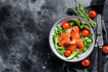 Salad with smoked salmon, arugula, avocado and cherry tomatoes. Concept for a tasty and healthy meal. Black background. Top view. Copy space.