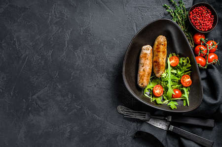 Grilled pork sausages with tomato and arugula salad. Black background. Top view. Copy space.