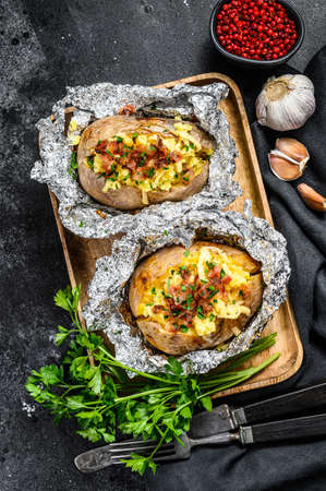 Tasty baked potato topped with cheddar cheese, garlic and parsley. Black background. Top view Reklamní fotografie