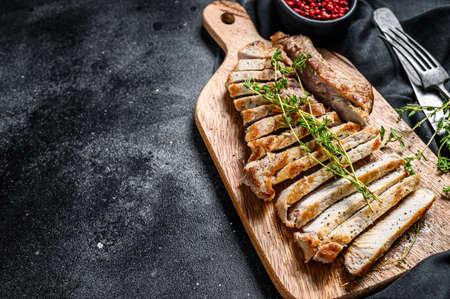 Grilled pork rib chop steak. Organic meat. Black background. Top view. Copy space