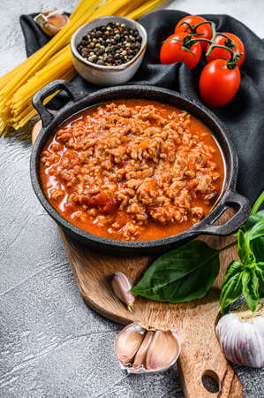 The concept of cooking Pasta bolognese spaghetti with tomatoes, cheese and basil. Gray background. Top view