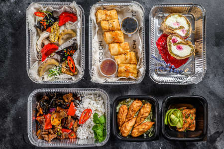 Choosing take away food. Spring rolls, dumplings, gyoza and dessert in lunch box. Take and go organic food. Thai and Asian traditional food. White background. Top view.