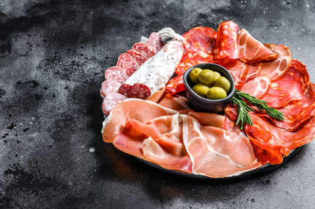 Spanish cold meat assortment. Chorizo, fuet, LOMO, jamon Iberico, olives. Black background. Top view. Copy space Reklamní fotografie