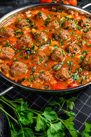 Pork meatballs with tomato sauce and vegetables in a pan. Black background. Top view