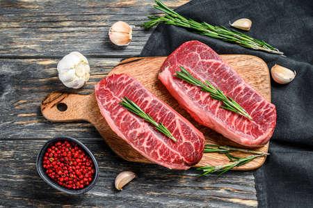 Raw marbled beef steak, top blade meat steak. Black background. Top view