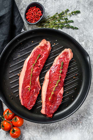 Raw strip loin steak on a grill pan, ingredients for cooking. Gray background. Top view