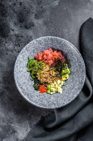 Tuna poke bowl with seaweed, avocado, cucumber, radish, sesame seeds. Black background. Top view Reklamní fotografie