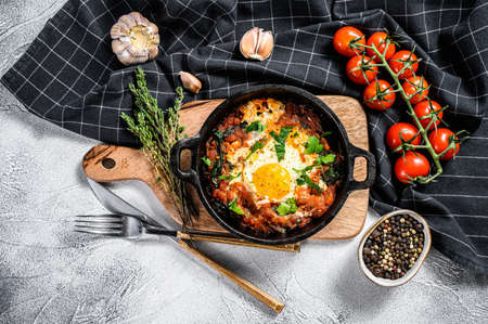 Homemade shakshuka, fried eggs, onion, bell pepper, tomatoes and parsley in a pan. Gray background. Top view