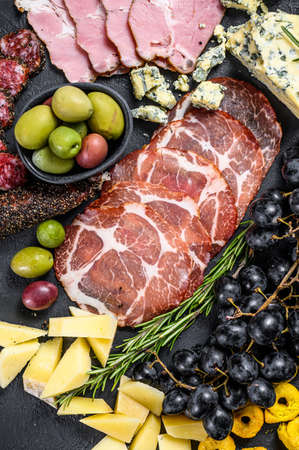 Typical italian antipasto with prosciutto, ham, cheese and olives. Black background. Top view Reklamní fotografie