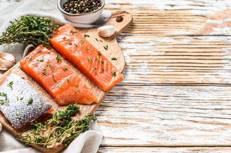 Salted salmon fillet with thyme. White wooden background. Top view. Copy space.