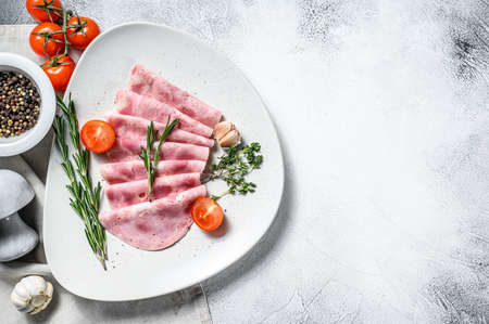 Sliced Pork ham. Fresh prosciutto. White background. Top view. Copy space. Stock fotó