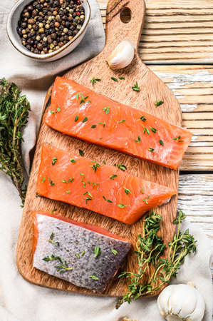 Salted salmon fillet with thyme. White wooden background. Top view.