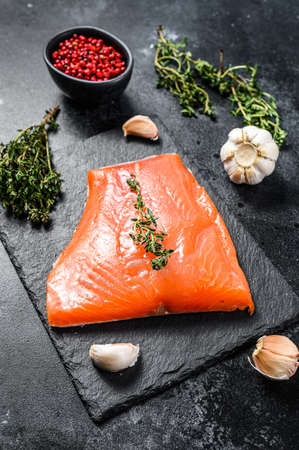Fresh raw salmon fillet with thyme. Black background. Top view.