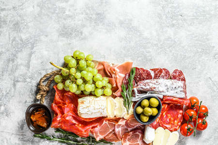 Italian antipasto, wooden cutting board with prosciutto, ham, parma, goat and Camembert cheese, olives, grapes. antipasti. Gray background. Top view. Copy space.