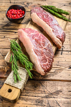 Raw picanha or Top Sirloin Cap steak on a chopping Board. wooden background. Top view.