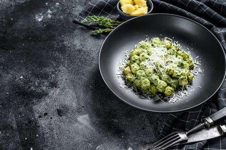 Gnocchi with basil spinach sauce and Parmesan. Italian potato paste. Black background. Top view. Copy space.