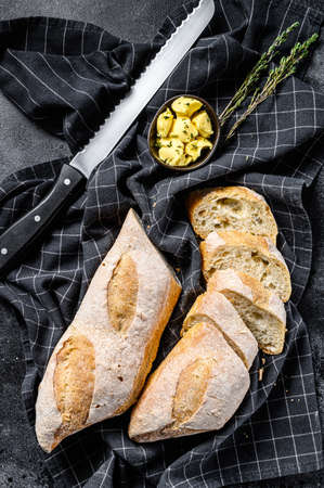 Artisanal baguettes and cut slice with butter. black background. top view