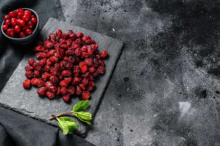 Organic dried cranberries on a stone Board. Black background. Top view. Copy space