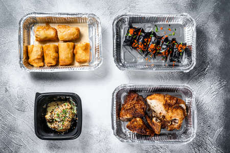 Different containers with delicious food. Delivery service. Asian cuisine, dumplings, spring rolls, dim sum, Peking duck. White background. Top view
