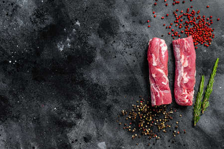 Fresh raw pork tenderloin with pepper and rosemary. black background. Top view. Copy space Reklamní fotografie
