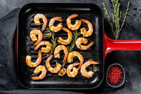 Fried king prawns, shrimps in a pan. Black background. Top view Reklamní fotografie
