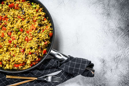 Cooked bulgur with vegetables and chicken meat in a pan. Gray background. Top view. Copy space Reklamní fotografie