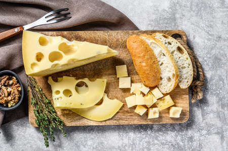 Yellow cheese with holes, dairy products. Gray background. Top view