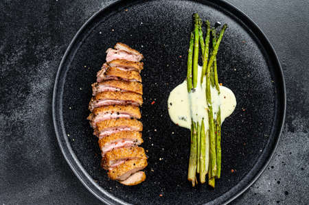 Grilled duck breast steak with baked asparagus. Black background. Top view Reklamní fotografie