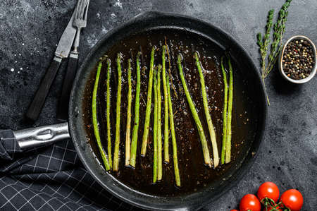 Cooking fresh Asparagus in a grilled pan. Black background. Top view Reklamní fotografie