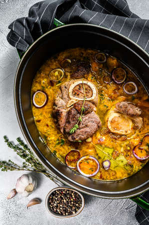 Cast iron pan with ossobuco made of cross cut veal shank. ossobuco meat stew. Gray background. Top view Reklamní fotografie