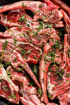 Raw fresh lamb rib chops marinated with thyme and mint in a pan. Black background. Top view Reklamní fotografie